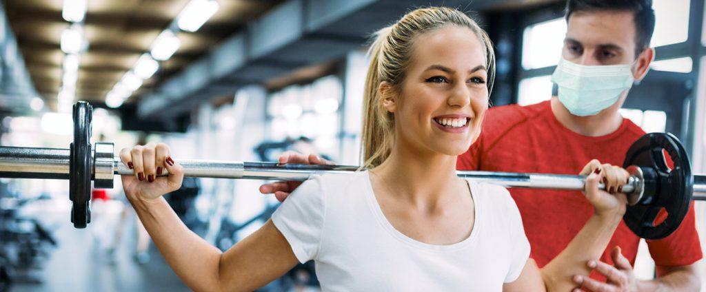 Lächelnde Frau wird bei ihrem Probetraining von Trainer mit Mund-Nasenschutz eingeleitet.